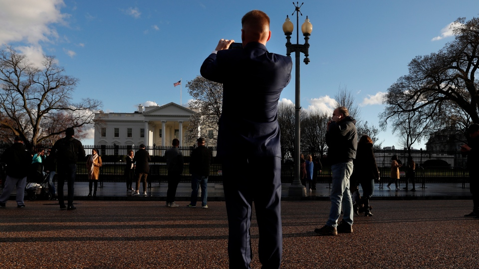 A man takes a photo of the White House, Friday March 22, 2019, in Washington, after news broke that special counsel Robert Mueller has concluded his investigation into Russian election interference and possible coordination with associates of President Donald Trump. (AP Photo/Jacquelyn Martin)