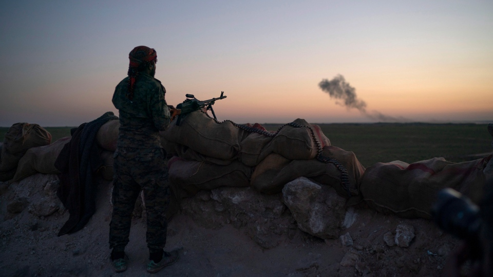 A U.S.-backed Syrian Democratic Forces (SDF) fighter looks as smoke billows after an airstrike hit territory still held by Islamic State militants in the desert outside Baghouz, Syria, Tuesday, Feb. 19, 2019. (AP Photo/Felipe Dana)