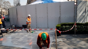Workers set up steel protections on the famed restaurant Fouquet's of the Champs Elysees in Paris, Friday, March 22, 2019. (AP Photo/Christophe Ena)