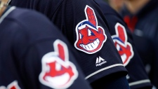 In this June 19, 2017 file photo, members of the Cleveland Indians wear uniforms featuring mascot Chief Wahoo as they stand on the field for the national anthem before a baseball game against the Baltimore Orioles in Baltimore. (AP Photo/Patrick Semansky, File)