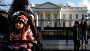 Tourists visit the White House with her family, Friday March 22, 2019, in Washington, as news breaks that special counsel Robert Mueller has concluded his investigation into Russian election interference and possible coordination with associates of President Donald Trump. (AP Photo/Jacquelyn Martin)