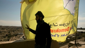 A U.S.-backed Syrian Democratic Forces (SDF) fighter stands on a rooftop overlooking Baghouz, Syria, after the SDF declared the area free of Islamic State militants after months of fighting on Saturday, March 23, 2019.  (AP Photo/Maya Alleruzzo)