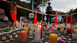 In this March 18, 2019, file photo, a student lights candle during a vigil to commemorate victims of March 15 shooting, outside the Al Noor mosque in Christchurch, New Zealand.  (AP Photo/Vincent Yu, File)