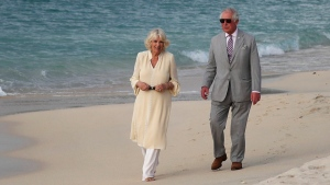 The Prince of Wales and the Duchess of Cornwall walk along Grand Anse beach during a one day visit to the Caribbean island of Grenada on Saturday March 23, 2019. (Jane Barlow / PA via AP)