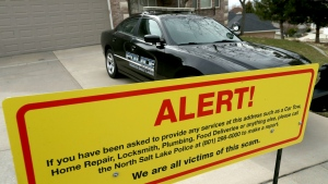 A warning sign and a police officer's vehicle are stationed at Walt Gilmore's home on Thursday, March 21, 2019.  (Laura Seitz/The Deseret News via AP)