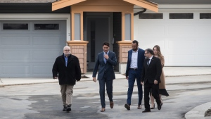 Prime Minister Justin Trudeau, second left, walks with first-time home buyers Marcus Malone, third left, and Bree Firth, back right, and MP's Ron McKinnon, left, and Dan Ruimy, front right, before a post-budget housing announcement at a townhouse development in Maple Ridge, B.C., on Monday March 25, 2019. THE CANADIAN PRESS/Darryl Dyck