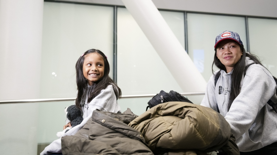 Vanessa Rodel and her seven-year-old daughter Keana arrive at Lester B. Pearson Airport in Toronto on Monday, March 25, 2019. THE CANADIAN PRESS/Christopher Katsarov