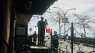 A White Rock, B.C. bylaw officer watches as a flag is removed from a Mexican restaurant. (Image provided)