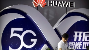 FILE - In this Sept. 26, 2018 file photo, a staff member uses a laptop at a display for 5G wireless technology from Chinese technology firm Huawei at the PT Expo in Beijing. (AP Photo/Mark Schiefelbein, File)