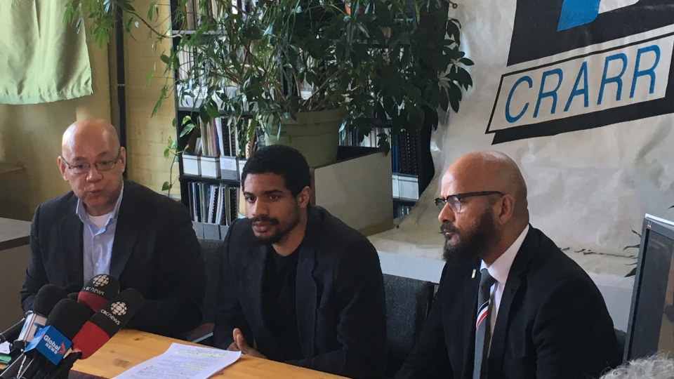 Juliano Gray, centre, speaks to reporters alongside Centre for Research-Action on Race Relations executive director Fo Niemi, left, and Alain Babineau, in Montreal on Tuesday, March 26, 2019. Gray was beaten with batons by transit inspectors on March 7 after being caught without a valid fare in an incident captured by a bystander. THE CANADIAN PRESS/Sidhartha Banerjee
