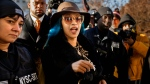 FILE - This Dec. 7, 2018 file photo shows Rapper Cardi B, center, arriving at Queens County Criminal Court in New York on charges related to a brawl at a New York strip club. (AP Photo/Andres Kudacki, File)