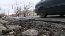 A car drives on a road covered in potholes.