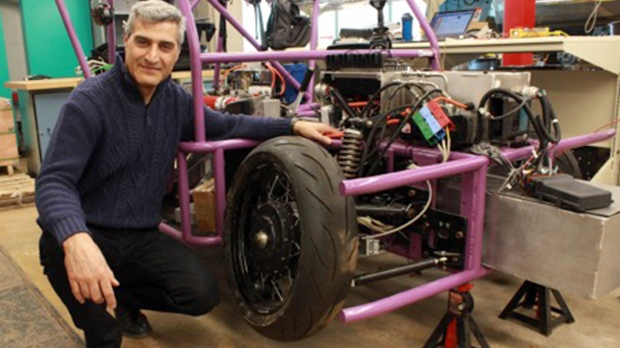 Amir Khajepour poses next to a vehicle prototype containing a corner module unit which could make it easier to produce low-cost specialized vehicles. (University of Waterloo)