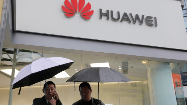 In this Thursday, March 7, 2019 file photo, two men use their mobile phones outside a Huawei retail shop in Shenzhen, China's Guangdong province. (AP Photo/Kin Cheung, File)