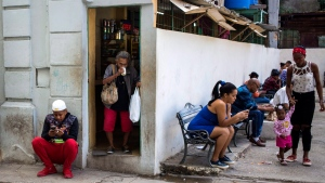 People surf the internet on their smartphones on the side of a plaza in Havana, Cuba, Thursday, Dec. 6, 2018. (AP Photo/Desmond Boylan)