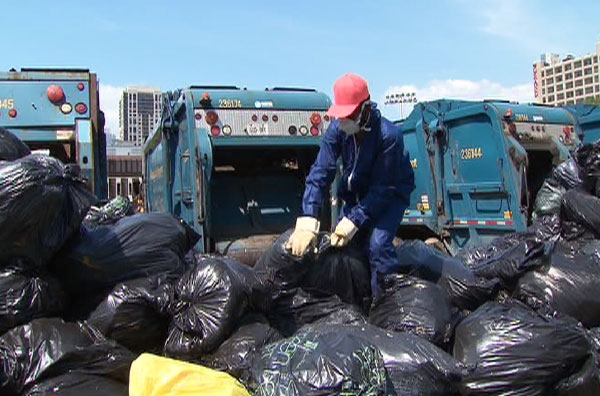 A city worker prepares to collect mounds of trash left at several temporary dump sites set up during the Toronto civic strike.