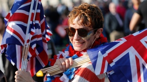 A woman holding Union Jack flags poses at Parliament Square in Westminster, London, Friday, March 29, 2019. (AP Photo/ Frank Augstein)