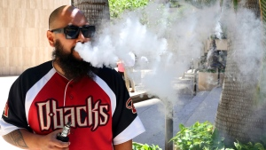 Trevor Husseini exhales a vape cloud in Honolulu on Thursday, March 28, 2019. (AP Photo/Audrey McAvoy)