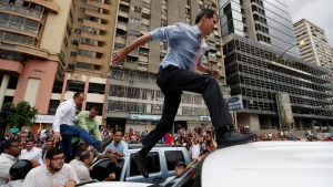 National Assembly President Juan Guaido, who declared himself interim president of Venezuela, leaps on to a vehicle to speak to supporters as he visits different points of anti-government protest in Caracas, Venezuela, on Tuesday, March 12, 2019. (AP Photo/Eduardo Verdugo)