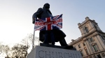 "A man holds a British flag with the words"" Leave Means Leave"" in front of the Winston Churchill statue during a rally by Brexit supporters in Westminster, London, Friday, March 29, 2019. Pro-Brexit demonstrators were gathering in central London on the day that Britain was originally scheduled to leave the European Union. (AP Photo/ Kirsty Wigglesworth)"