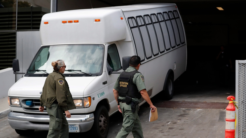 In this Tuesday, March 19, 2019 file photo, a van carrying asylum seekers from the border is escorted by security personnel as it arrives to immigration court, in San Diego.  (AP Photo/Gregory Bull, File)