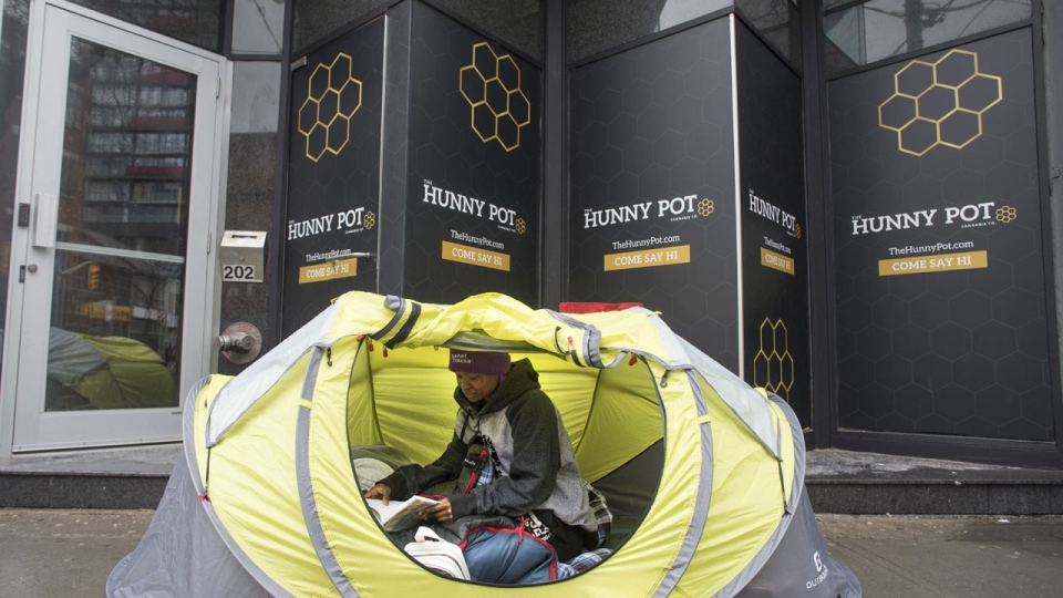Marie Kamara becomes the first in line, on Sunday March 31 , 2019, as she sits in her tent, outside the Hunny Pot Cannabis retail store, on Toronto's Queen Street which opens tomorrow morning. April 1 marks the first day that retailers who were successful in Ontario's lottery can open brick-and-mortar cannabis retail stores. THE CANADIAN PRESS/Chris Young