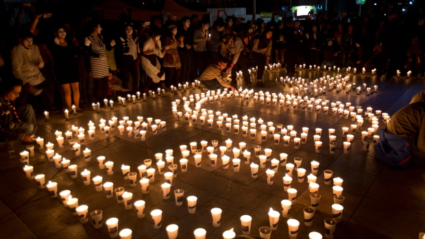 People gather near the arrangement of candles that form the number 60, to represent the minutes in an hour, during the Earth Hour in La Paz, Bolivia, Saturday, March 30, 2019. Earth Hourtakes place worldwide and is a global call to turn off lights for 60 minutes in a bid to highlight the global climate change. The Earth Hour was started in Australia in 2007, which has become a global event. (AP Photo/Juan Karita)