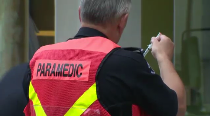 A paramedic holds a needle containing an unknown drug.