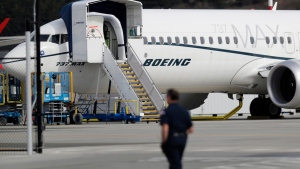 FILE - In this March 14, 2019, file photo, a worker walks next to a Boeing 737 MAX 8 airplane parked at Boeing Field in Seattle.  (AP Photo/Ted S. Warren, File)