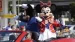 Disney characters Minnie Mouse, right, and Mickey Mouse, rear, ride in the Three Kings Day Parade in Miami, on Jan. 12, 2014. (Wilfredo Lee / AP)