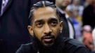 FILE - This March 29, 2018 file photo shows rapper Nipsey Hussle at an NBA basketball game between the Golden State Warriors and the Milwaukee Bucks in Oakland, Calif. (AP Photo/Marcio Jose Sanchez, File)