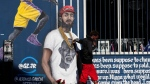A man touches a mural depicting slain rapper Nipsey Hussle, Tuesday, April 2, 2019, in Los Angeles. Hussle was shot and killed Sunday, March 31, outside of his clothing store in Los Angeles. (AP Photo/Jae C. Hong)