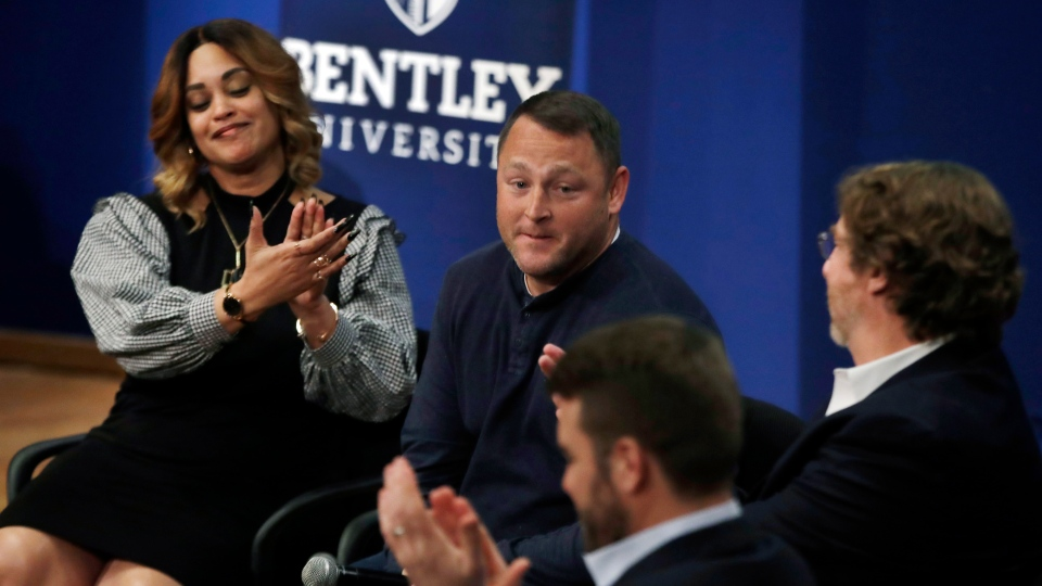 In this March 5, 2019 photo, panel members including Natalie Baucum, left, applaud Mike Duggan, middle, during an event at Bentley University, in Waltham, Mass., where professors and alumni shared some of their worst setbacks to illustrate that even successful people sometimes fail. (AP Photo/Elise Amendola)