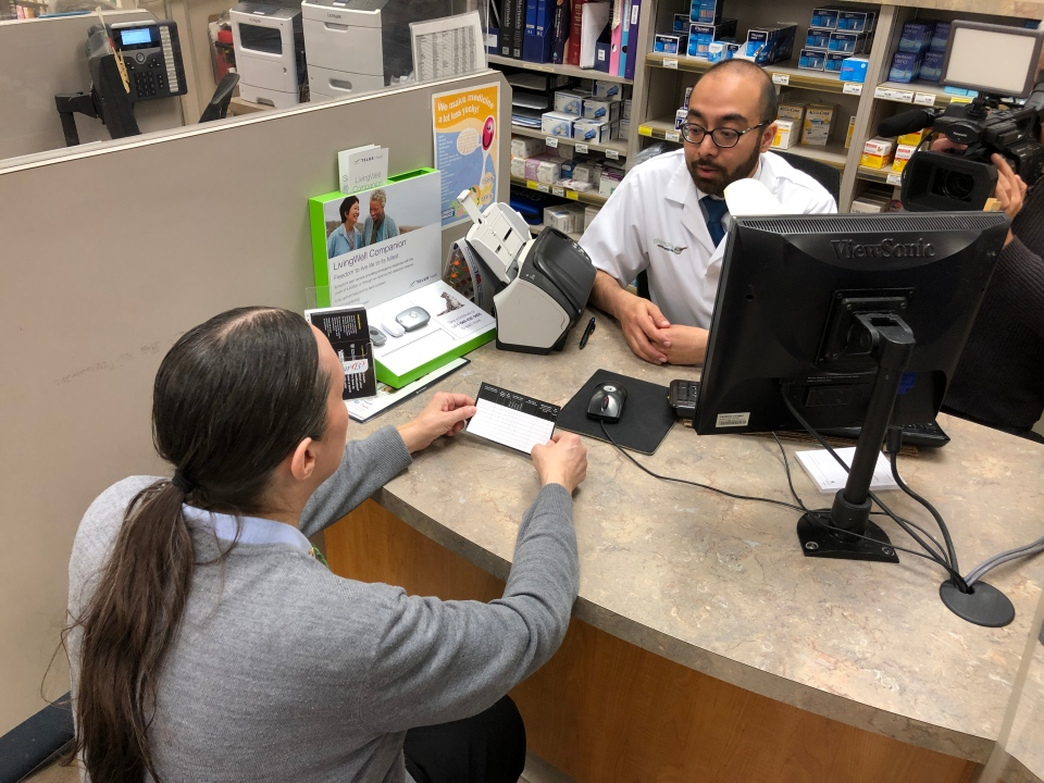 A patient holds a medications card while speaking to a pharmacist. (Christian Adler / CTV News Vancouver)
