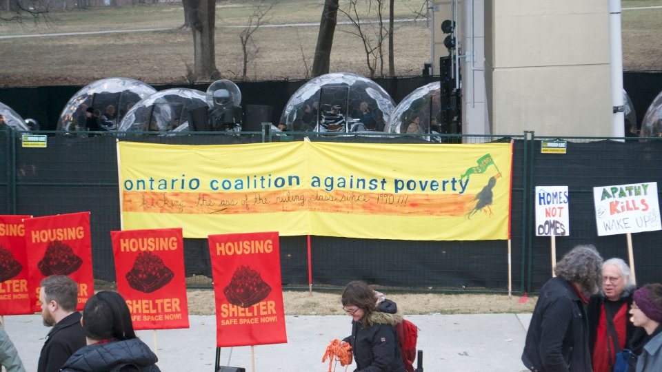 Activists with the Ontario Coalition Against Poverty getting ready to protest a pop-up dinner held in furnished glass domes on April 5, 2019. (Photo by Doha Hanno)