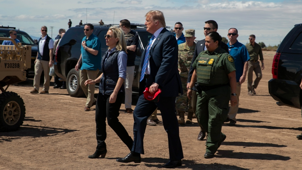 U.S. President Donald Trump walks with Homeland Security Secretary Kirstjen Nielsen as they visit a newly constructed part of a border wall with Mexico in Calexico, Calif., Friday April 5, 2019. (AP Photo/Jacquelyn Martin)