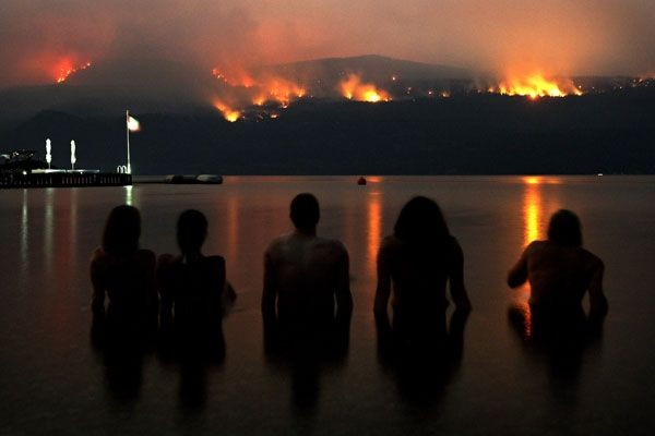 A group of friends sit in Lake Okanagan as they watch wildfires burn on Terrace Mountain north of Kelowna, B.C., in the early morning hours of Tuesday August 4, 2009. (Darryl Dyck / THE CANADIAN PRESS)