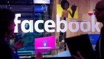FILE - In this April 18, 2017 file photo, conference workers speak in front of a demo booth at Facebook's annual F8 developer conference, in San Jose, Calif. (AP Photo/Noah Berger, File)