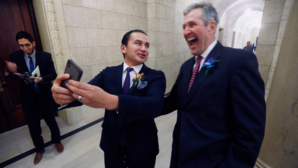Manitoba Premier Brian Pallister, right, and Manitoba NDP Leader Wab Kinew pose for a selfie after the reading of the throne speech at the Manitoba Legislature in Winnipeg, Tuesday, Nov. 20, 2018. (THE CANADIAN PRESS/John Woods)