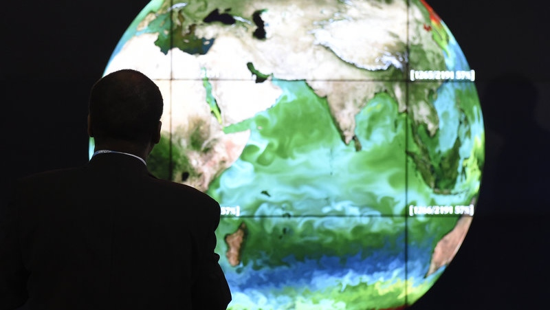 A conference attendee looks at a projection of Earth on the opening day of the COP 21 United Nations conference on climate change, in November on the outskirts of Paris. (Alain Jocard/AFP)