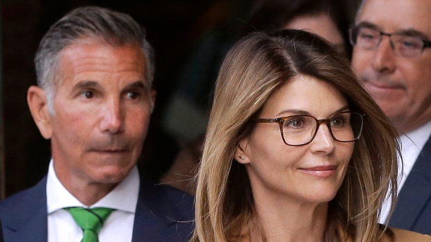 """In this April 3, 2019 file photo, """"Full House"""" star Lori Loughlin, front, and husband, clothing designer Mossimo Giannulli, left, depart federal court in Boston after facing charges in the scandal. (AP Photo/Steven Senne, File)"""