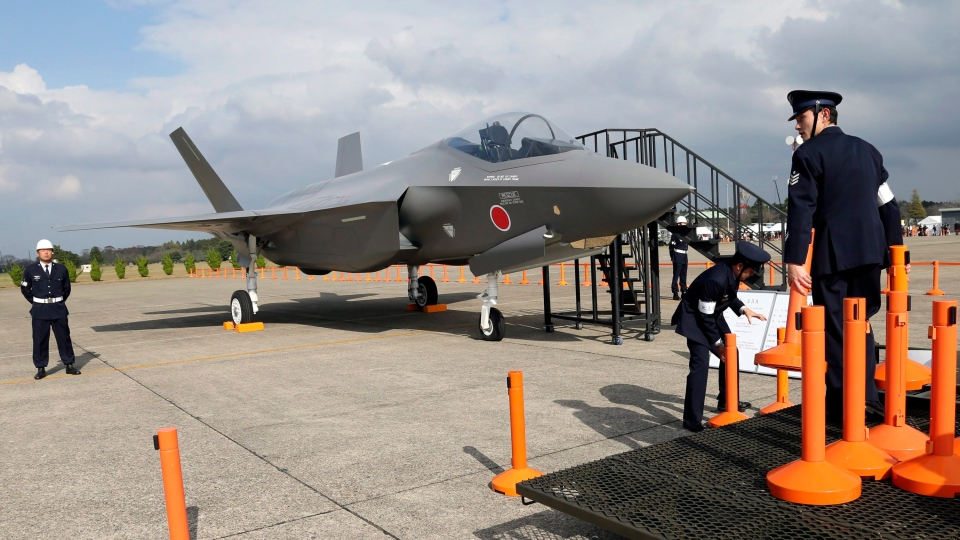 In this Oct. 26, 2014, file photo, Japan Air Self-Defense Force crew members set up cordons to protect a mockup of the F-35 fighter jet during the annual Self-Defense Forces Commencement of Air Review at Hyakuri Air Base, north of Tokyo. (AP Photo/Eugene Hoshiko, File)