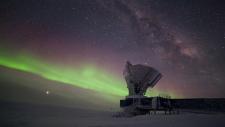 The South Pole Telescope illuminated by aurora australis and the Milky Way. (Photo: Daniel Michalik / South Pole Telescope)
