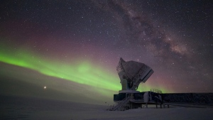 The South Pole Telescope illuminated by aurora australis and the Milky Way. (Photo: Daniel Michalik / South Pole Telescope)