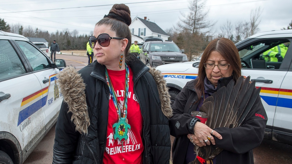 Michelle Paul, left, and Dorene Bernard, Mi'kmaq protesters, stand at an RCMP roadblock in Fort Ellis, N.S. on Wednesday, April 10, 2019.  (THE CANADIAN PRESS/Andrew Vaughan)