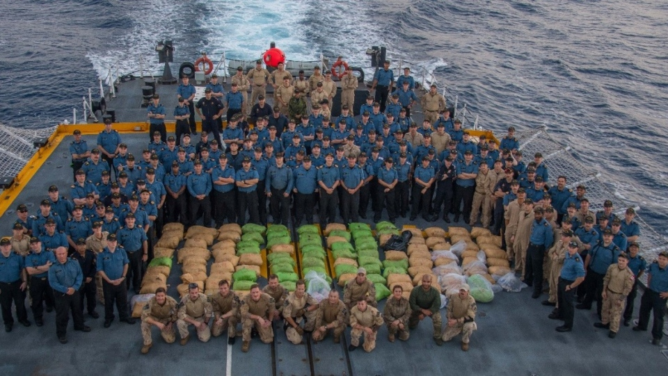 Crew members of HMCS Regina pose with more than 2,500 kilograms of hashish seized during Operation Artemis, April 7, 2019. (Corp. Stuart Evans, BORDEN Imaging Services)