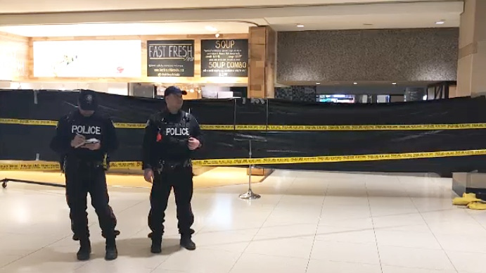 Toronto police officers guard a fast food stall in the city's PATH system on April 11, 2019 after a woman was stabbed to death one day earlier.