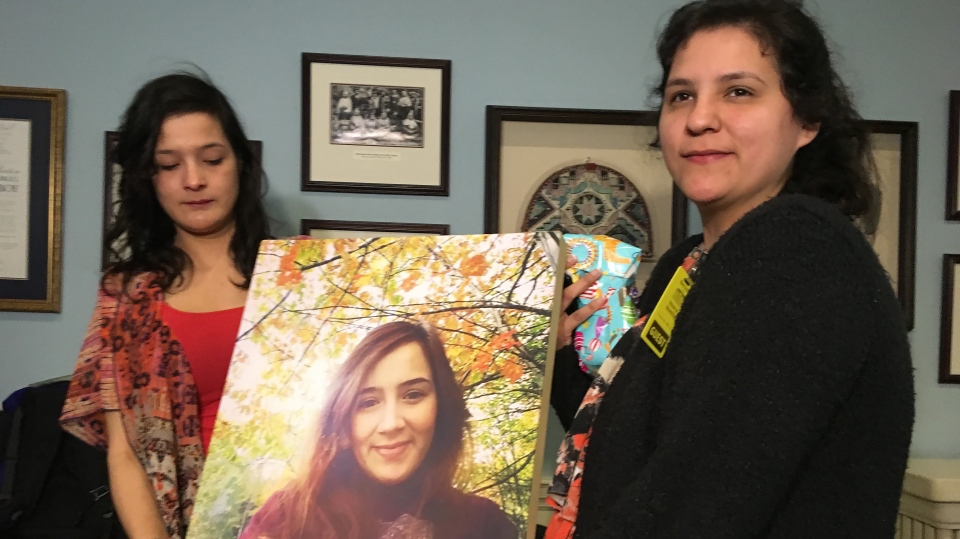 Tyra Denny, left, and Renee Denny hold a photo of their sister Cassidy Bernard at the Nova Scotia legislature in Halifax on Thursday, April 11, 2019. (THE CANADIAN PRESS/Michael MacDonald)
