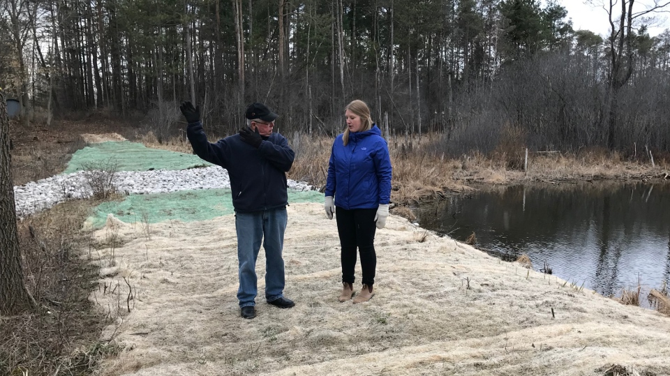 Rick Faulds of the Delaware Sportsmen's Association and Rachael Scholten of Ducks Unlimited walk along the retrofitted dam near Delaware, Ont. on Thursday, April 11, 2019. (Sean Irvine / CTV London)