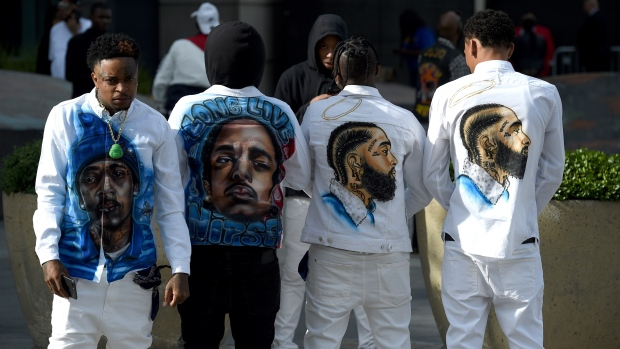 Slum Baby, from left, Yhung To, Lil Cadi PGE and Lo, from the Crenshaw neighborhood of Los Angeles, wear clothing in honor of Nipsey Hussle, whose given name was Ermias Asghedom, at the late rapper's Celebration of Life memorial service on Thursday, April 11, 2019, at the Staples Center in Los Angeles. (Photo by Chris Pizzello/Invision/AP)